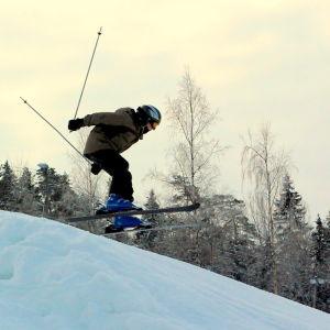 En pojke med brun jacka och svart hjälm hoppar med sina skidor över ett gupp i en slalombacke.
