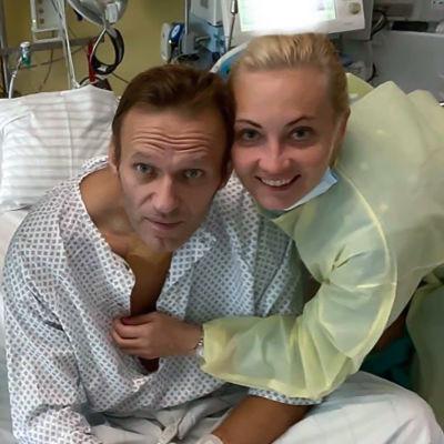 En patient i en sjukhussäng omgiven av sjuksköterskor.