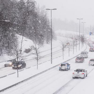 Autoliikenne lumisateessa.