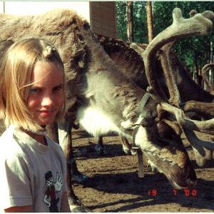 Kandit-ohjelman eläinlääkärikandi Veera pienenä tyttönä poron vierellä