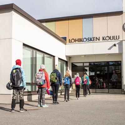 Oppilaat jonottavat Lohikosken koululle pitäen turvavälit.