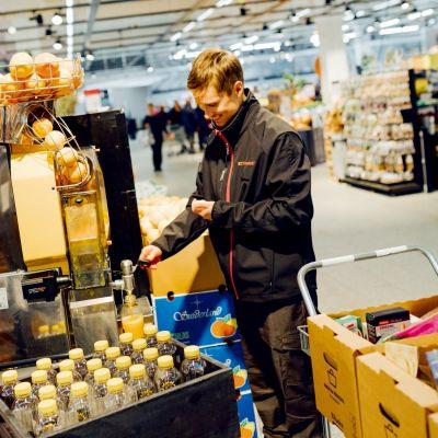 myyjä puristaa appelsiinimehua kaupassa