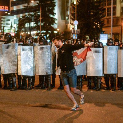 Mielenosoittaja juoksee lipun kanssa mellakkapoliisin edessä