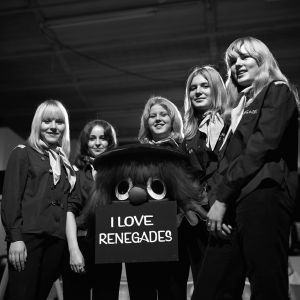 """The Renegades -yhtyeen faneja ja peikkonukke, joka kantaa kylttiä """"I love Renegades""""."""