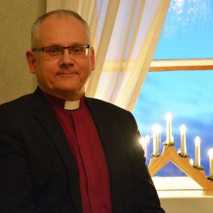 En medelålders man står invid ett fönster där en elljusstake lyser. Mannen har på sig en svart kavaj, en röd skjorta och en prästkrage.