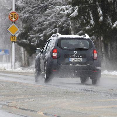 Auto ajaa räntäisellä tiellä.