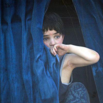 Poika katselee bussinikkunasta ulos Itä-Ghoutassa, Damaskuksessa.