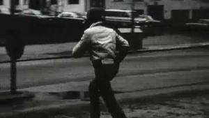 Nuori poika kiirehtii kadun yli. Hänellä on kiire kirjastoon.