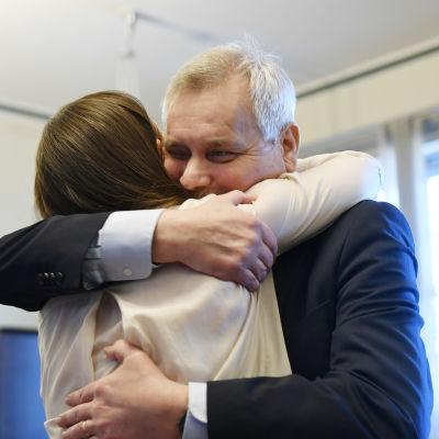 Antti Rinne, en äldre man med grått hår i kostym omfamnar Sanna Marin. Kvinnan har en ljus tröja och brunt hår.