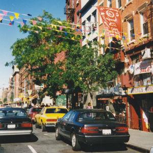 Manhattanilainen katunäkymä 1990-luvulta. Kuvassa autoja ja kauppojen julkisivuja.