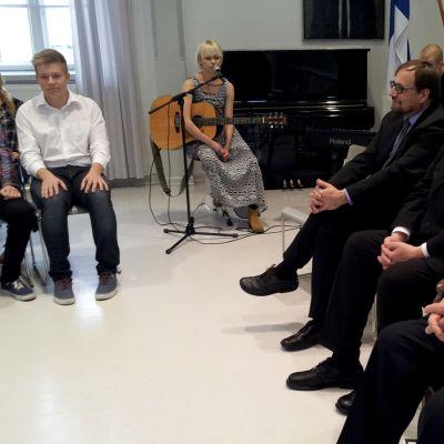 Presidentti Martti Ahtisaari istuu miesten ja koululaisten kanssa