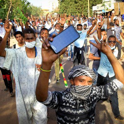 Sudanilaiset mielenosoittajat marssivat kadulla.