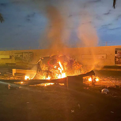Ett brinnande vrak på en väg. Det ligger brända delar överallt. I bakgrunden en mur.