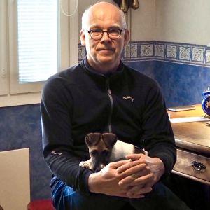 Markus Ukkonen työpöytänsä edessä sylissään Joppe-koira.