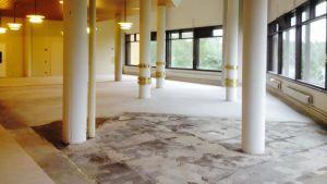 En hall med vita pelare och golv som renoveras. Ljus strömmar in genom fönstren.