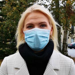 En kvinna med långt ljust hår och rutig kappa står i ett höstigt landskap och har ett munskydd i ansiktet.