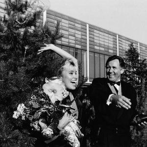 Tuore tangokuningatar Arja Koriseva tuuletta kukkakimppu kainalossaan vieressään tangokuningas.