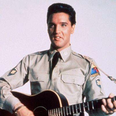 Elvis Presley bär militäruniform och spelar akustisk gitarr.