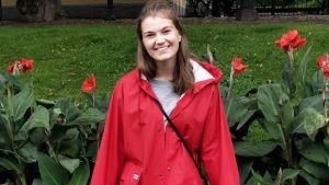 En leende ung kvinna i röd regnrock.