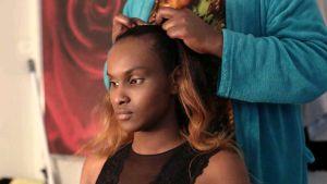 Närbild på Kelet då hon sitter på en stol och får frisyren gjord.