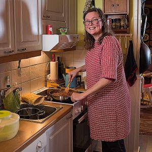 kvinna lagar mat och man i bakgrunden