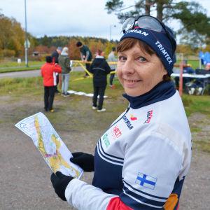En kvinna i vindjacka och mössa håller i en karta och tittar in i kameran. Hon står utomhus och bakom henne syns andra människor.