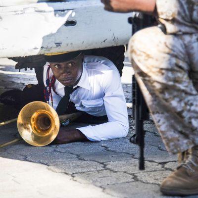 Haitin kansallispalatsin orkesterin jäsen suojautuneena auton alle soittimensa kanssa mellakan alkaessa.