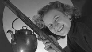 Hymyilevä nainen pitelee luudanvartta, jossa roikkuu kahvipannu.