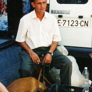 Tutkija Taina Kinnunen maailmankuva muuttui, kun hän todisti eläinten kaltoinkohtelua. Kuvassa mies pitää kiinni ketjusta, joka on kiinnitetty koiraemon kaulaan. Koiran viereissä korissa on myynnissä olevia pentukoiria.