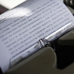 Paperi ja sille kirjoitettua tekstiä mekaanisessa kirjoituskoneessa.