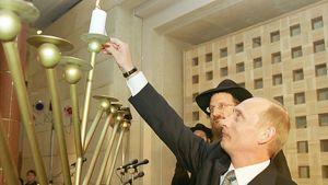 Vladimir Putin tänder ljus i en hannukah-menorah tillsammans med rabbinen Berel Lazar i december 2000.