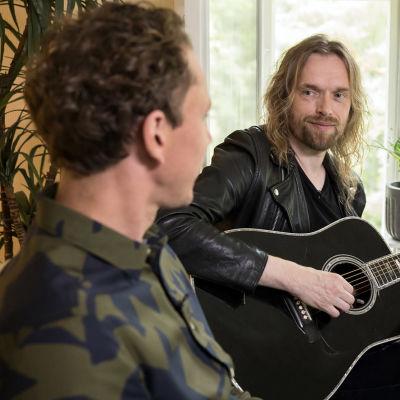 Juha Itkonen ja Anssi Kela keskustelevat. Kelalla on kitara kädessään.