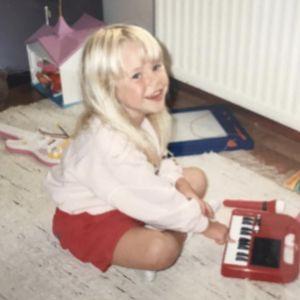 Krista Siegfrids som barn spelar på leksakspiano på golvet.