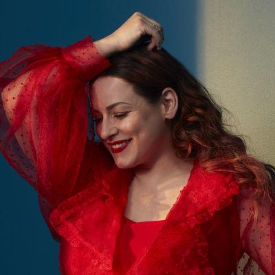 Laulaja Erin poseeraa katsoo poispäin kamerasta. Hänellä on yllään punainen, dramaattinen mekko.
