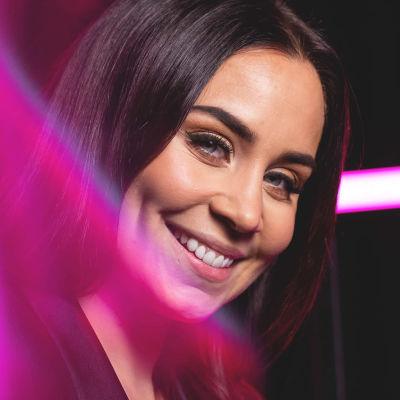 Ruskeahiuksinen laulaja Abreu katsoo hymyillen kameraan pää kallellaan, etualalla neonpinkkejä valoelementtejä.
