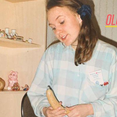 Teini-ikäinen Mira Luoti istuu huoneessaan. Kädessään hänellä on banaani, jonka päälle on puettu kodomi.