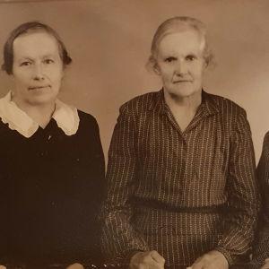 Kolme mutturapäista paitamekkoista naista istuu vakavina vierekkäin.