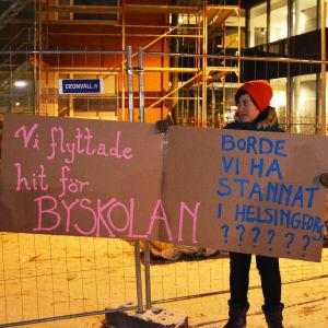 En kvinna står utomhus och håller i två skyltar där det står: Vi flyttade hit för byskolan borde vi ha stannat i Helsingfors?