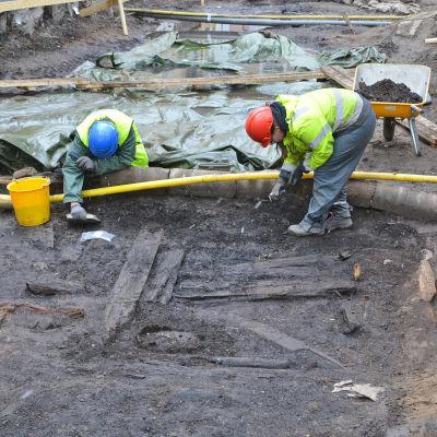 Två personer i gula västar gräver i jorden.