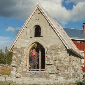Mies kurkistaa pienen, rakenteilla olevan kirkon oviaukosta.