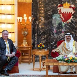 USA:s utrikesminister Mike Pompeo och Bahrains kung Hamad bin Isa Al Khalifa sitter i röda sammetsfatöljer och ler mot kameran.