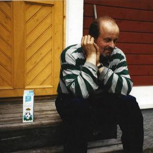 Kari Alonen istuu pajan rappusilla maitotölkin vieressä.