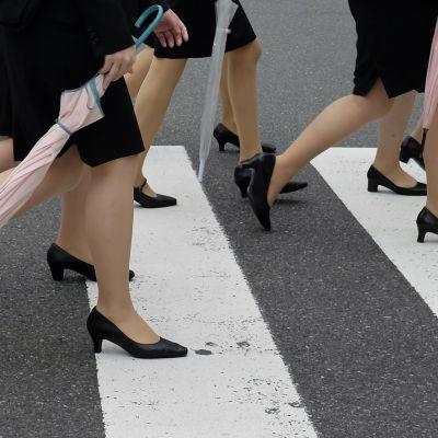Suojatietä ylittävien naisten jalkoja.