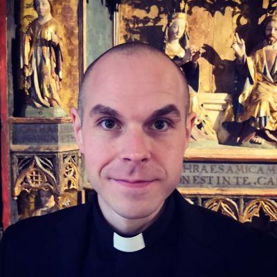 Kirkkoherra kirkossa papin virka-asussa.