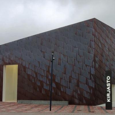 Utsidan av biblioteket Fyyri. Det är en mulen dag, biblioteket är rostbrunt och har en skylt med ordet Kirjasto i lysande bokstäver utanför huvudentren.
