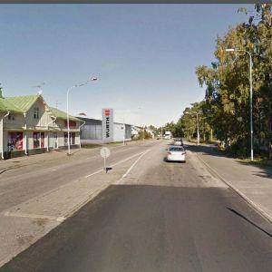Ett bildmontage visar hur företaget Würts affär, en lagerförsäljning, skulle se ut vid Märsgatan i Hangö. En asfalterad sliten gata som kantas av trähus och andra byggnader. Den tilltänkta affären syns på högra sidan av gatan till vänster. Sommar, sol.
