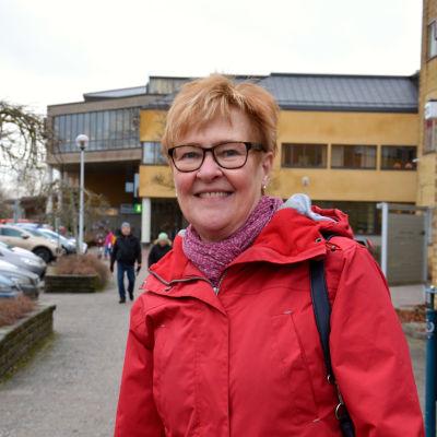 Gunni ler glatt i en röd jacka och står utomhus nära stadshuset i Pargas.