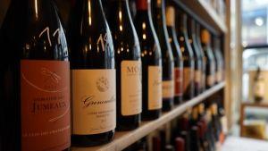 Viinipulloja kaupan hyllyssä.