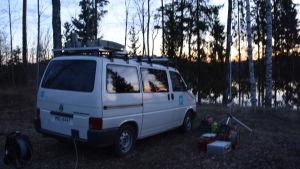 Valkoinen Ylen ulkolähetyspakettiauto järven rannalla.
