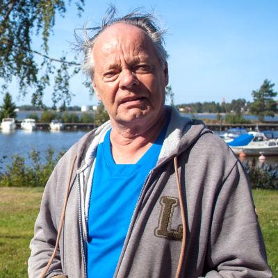 Christian Nylund på en strand, i bakgrunden ett gammalt skeppsankare.